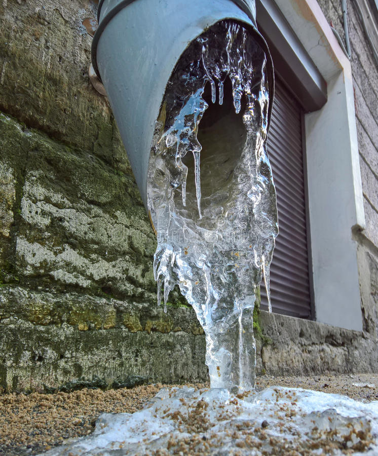 Drain pipe with frozen water. On the wall stock photography