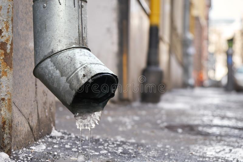Drain pipe with frozen water in winter on Moscow street. Metal drain pipe with frozen water in winter on Moscow street royalty free stock photo