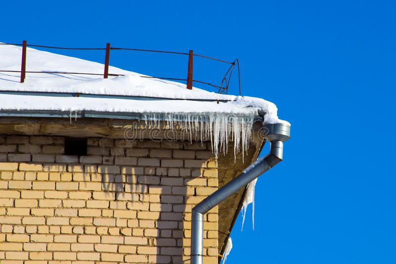 The drain pipe and icicles on the roof edge of the building stock images