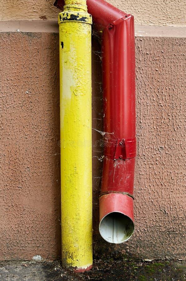 Drain rouge de drain de pluie et de gazoduc jaune photos stock