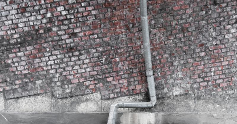 A drainpipe for rain in front of a brick wall. A curved drainpipe for rain in front of a brick wall royalty free stock photography