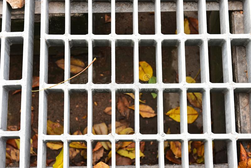 Drains from the roof at the time of rain. The water drain made from steel surrounded by concrete royalty free stock photo