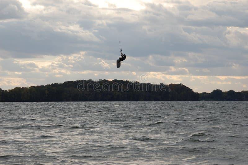 Drakeboarderen hoppar ovanför träd royaltyfri foto