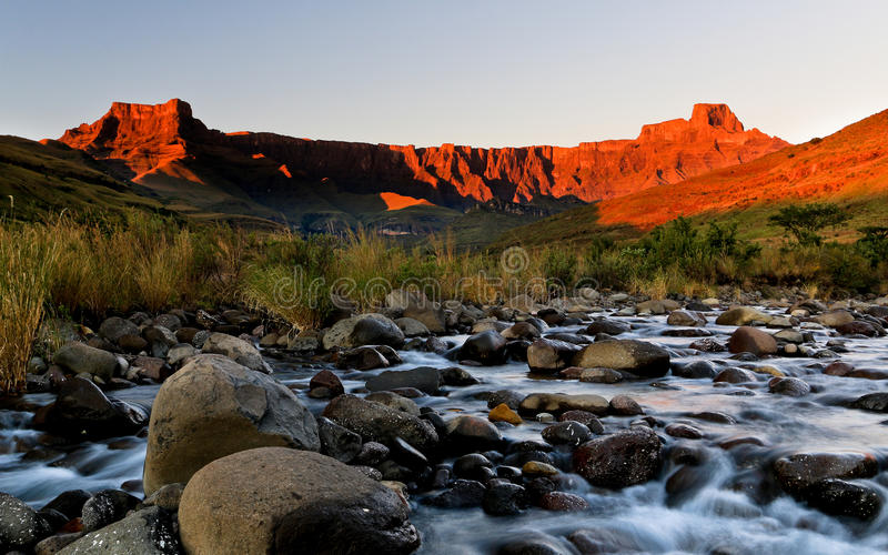 Drakensberg Amphitheatre Golden Sunrise. Morning light fills the scene with golden light, lighting up the mountain in perfect colours. the Tugels river slows royalty free stock photography