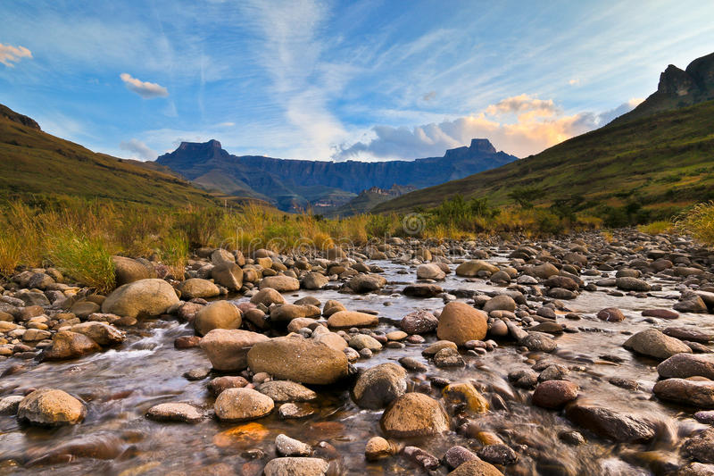Drakensberg Amphitheatre sunset. Clouds are lit up by the last rays of golden light, filling the scene with a lovely calm feeling. Drakensberg mountains, south stock photography