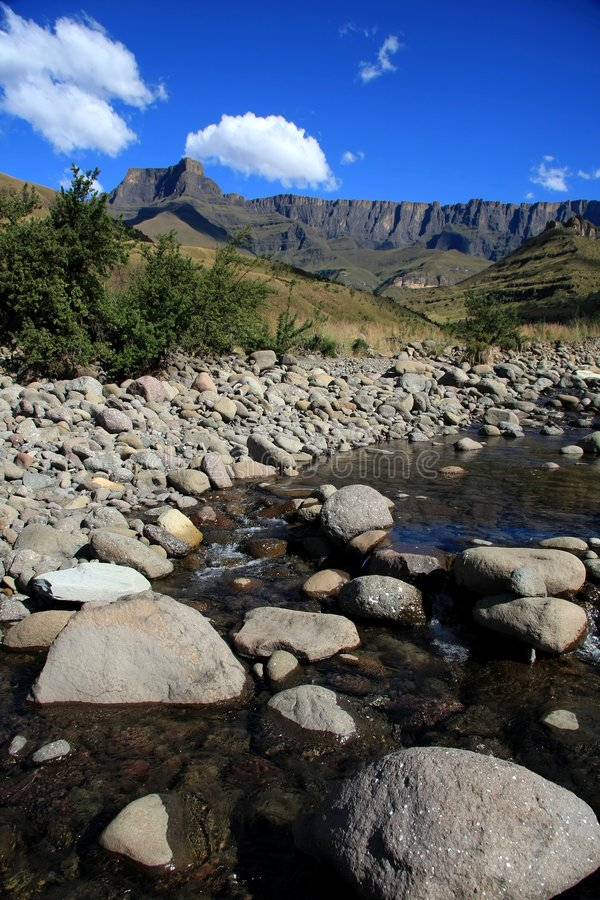 Drakensberg Mountains. The beautiful Drakensberg Mountains and a stream or river in South Africa royalty free stock images