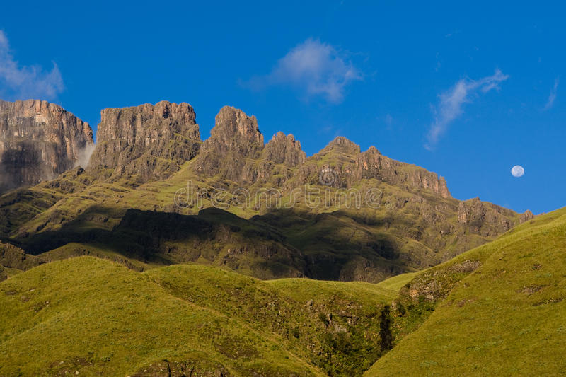 Drakensberg peaks. A photo of the Drakensberg with green grass and blue skies, as well as the moon royalty free stock image