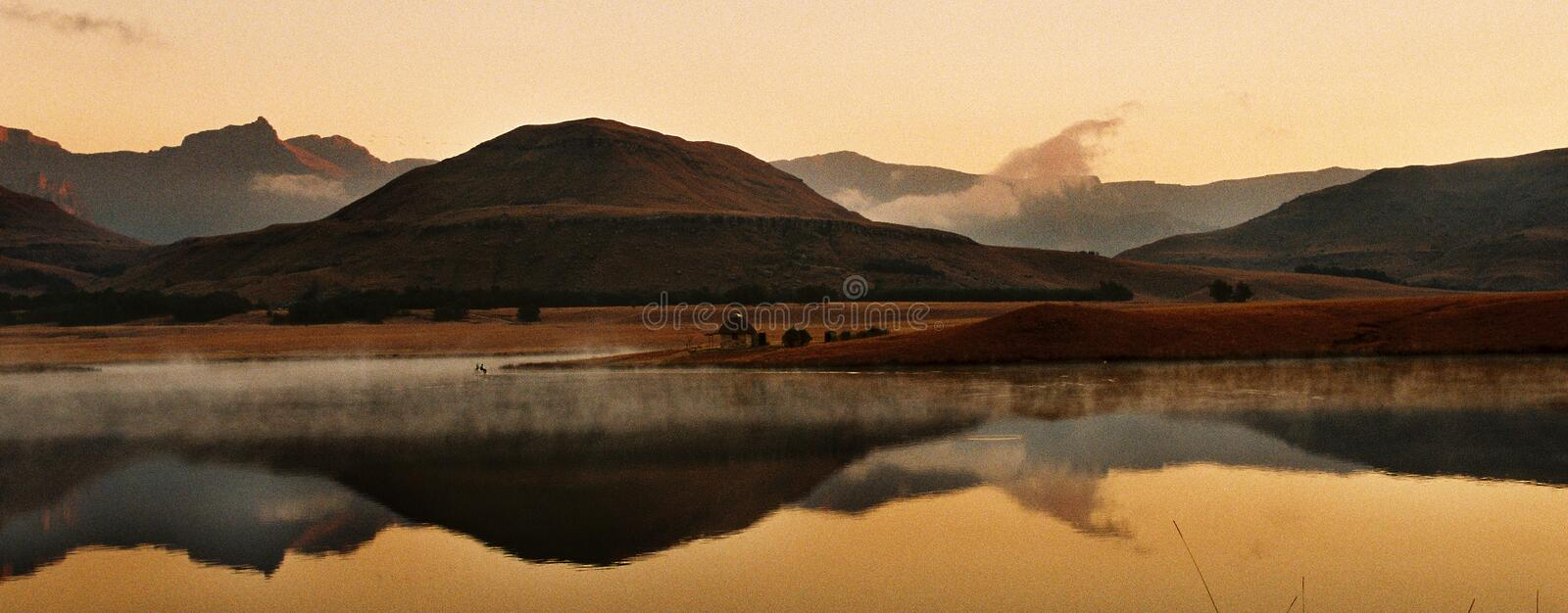 Drakensberg Sunset. A typical early winter sunset over a dam in the Kzn Drakensberg stock photography