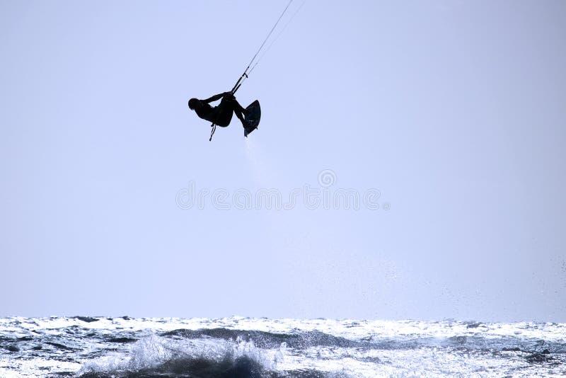Drakesurfare med sprej av vatten bakom i luften arkivbild