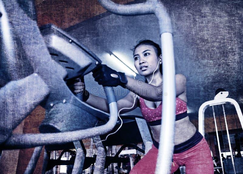 Dramático corrija de la mujer asiática sudorosa atractiva joven que entrena difícilmente en el gimnasio usando la máquina pedalin foto de archivo libre de regalías