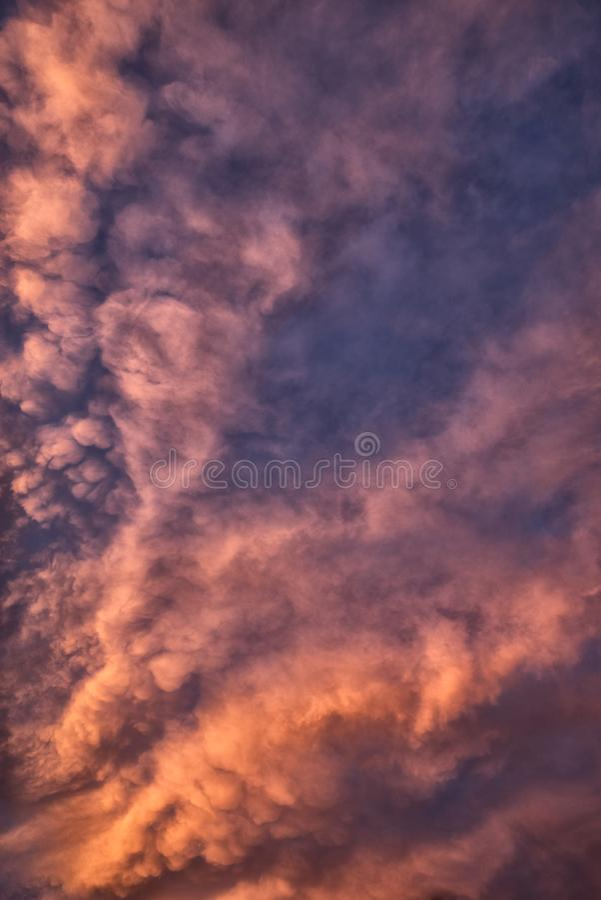 Drama i himlen Mammatus och cirrusmolnmoln som glöder på solnedgången över Surrey, England royaltyfri bild