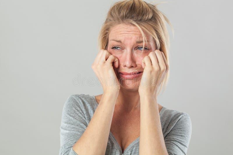Drama para la mujer rubia que llora con los rasgones grandes que expresan la decepción imagen de archivo