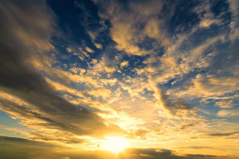 Dramadic日落天蓝色和太阳的橙色光通过在天空的云彩 图库摄影