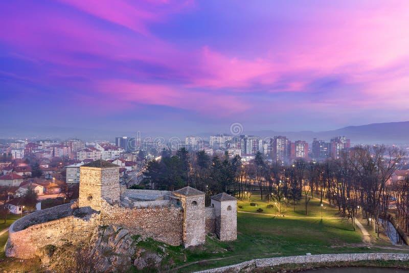Dramat i himlen, den forntida fästningen och staden tänder under dimmig blå timme arkivfoton