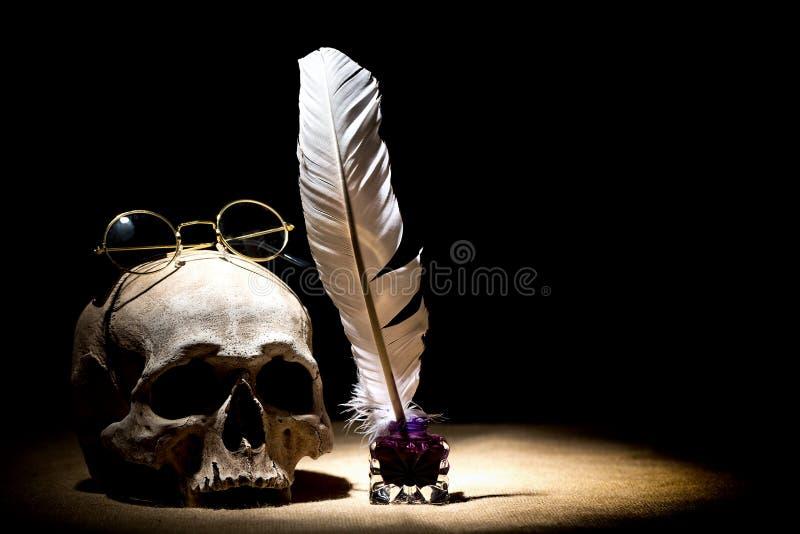 Dramata lub teatru pojęcie Stary kałamarz z piórkową dutką blisko czaszki z starymi retro szkłami przeciw czarnemu tłu dramatyczn obrazy stock