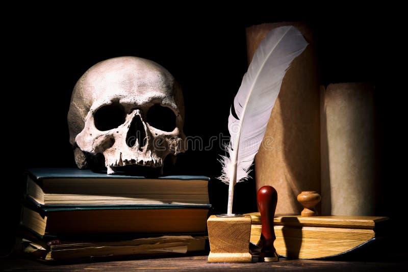 Dramata, teatru lub literatury pojęcie Stary kałamarz z piórkowymi pobliskimi ślimacznicami z czaszką na książkach przeciw czarne obraz stock
