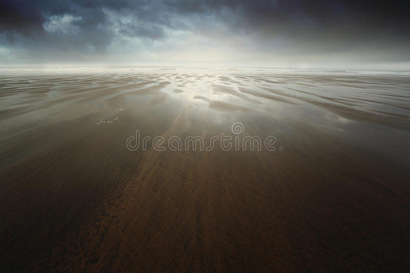 Dramatic beach with dark cloudscape royalty free stock photos