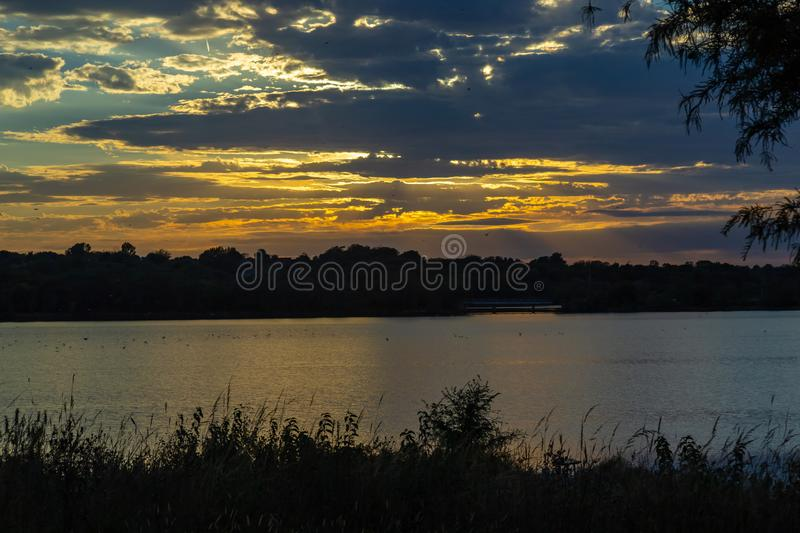 Dramatic beautiful clouds at sunset over lake Zorinsky Omaha Nebraska. Dramatic skyline of the setting sun with beautiful clouds golden sun reflection on the royalty free stock photos