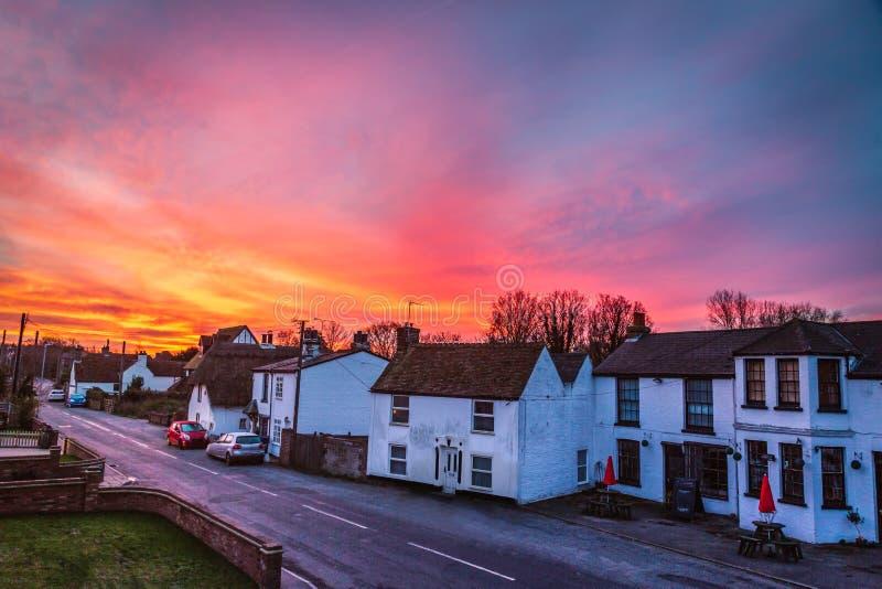 Dramatic and beautiful sunrise illuminating the sky over the quaint white cottages and terrace houses of Monkton, Kent, UK royalty free stock photo