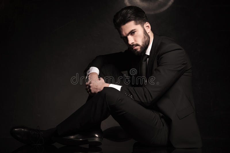 Dramatic business man sitting on the floor stock photography
