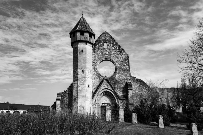 Dramatic church ruins in black and white, with a few tombstones in front. Carta monastery is a former Benedictine church. stock photography