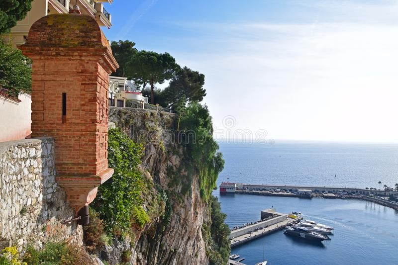 A dramatic cliff with green trees & brick structure and harbour view of the Principality of Monaco. Monaco is a sovereign city-state, country and microstate on stock photo