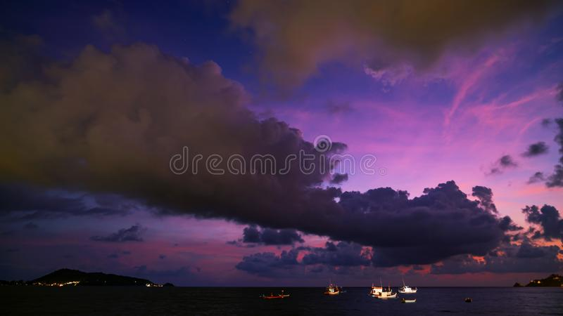 Dramatic clouds Amazing colorful majestic sky over sea in evening time,Dark Blue​ Hour Silhouette mountain and boats on twilight stock photography