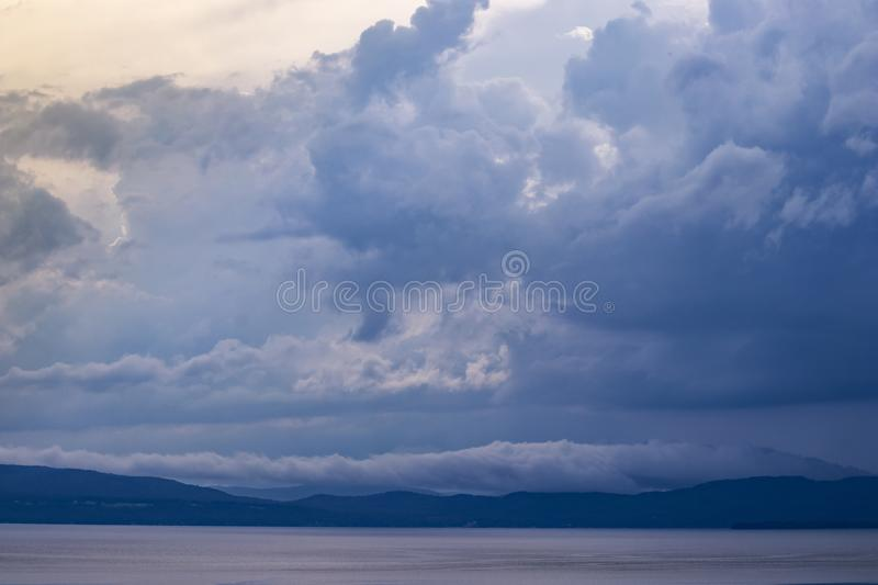 Dramatic clouds over lake and mountains at dusk. Dramatic blue and purple clouds over lake and mountains at dusk stock images