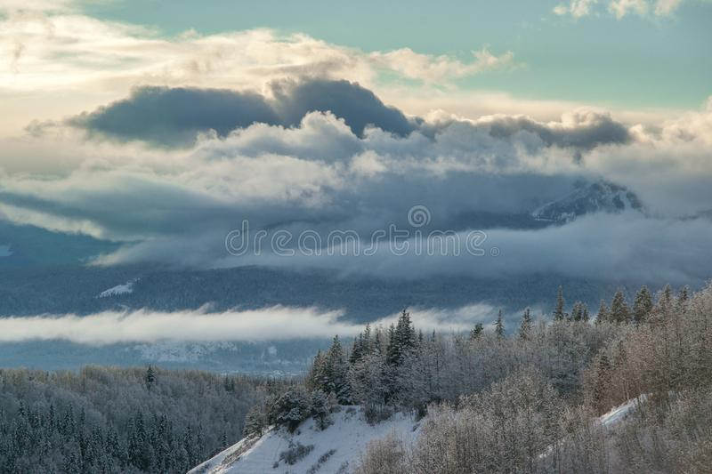 Dramatic Clouds over Smithers. Dramatic clouds cover Hudson Bay Mountain just west of the Yellowhead Highway town of Smithers in BC, Canada stock photo