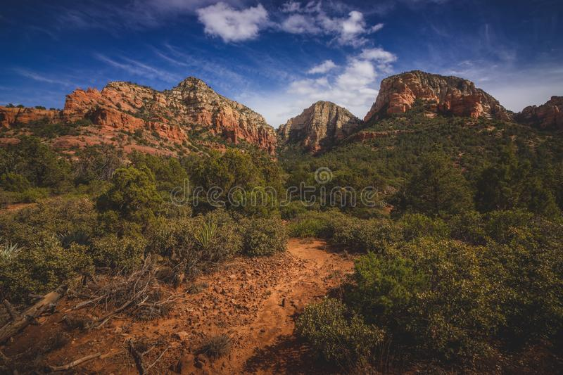 Dramatic Cloudscape over Capitol Butte. Dramatic blue sky and cloudscape over Capitol Butte aka Thunder Mountain from Vultee Arch hiking Sedona, Arizona royalty free stock images