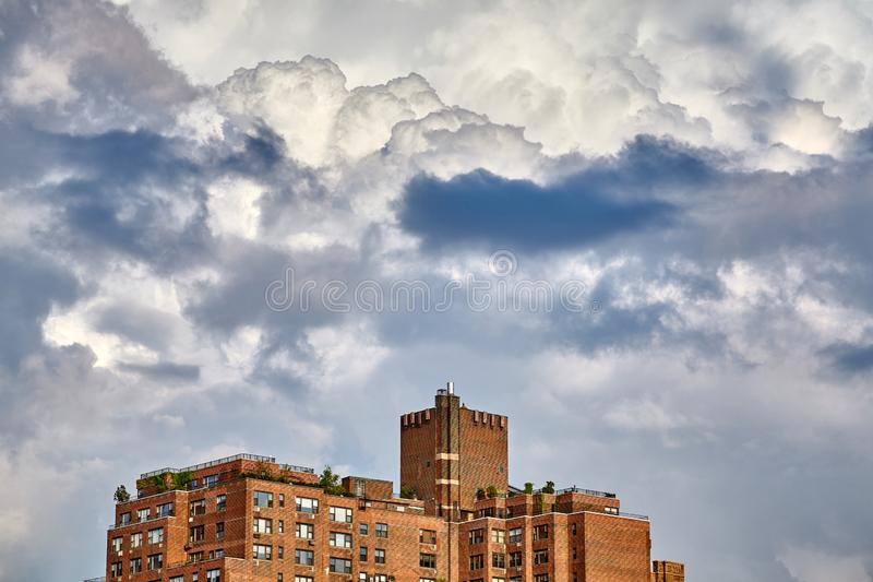 Dramatic cloudscape over an old residential building in New York. royalty free stock image