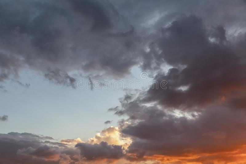 Dramatic cloudscape with fiery red sunset 145. Dramatic cloudscape skies with fiery red and dark grey clouds. Some blue sky ahowing through the clouds royalty free stock images