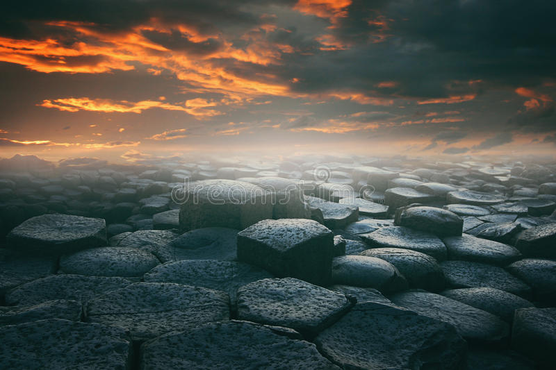 Dramatic cloudscape and stone beach. Dramatic cloudscape and hexagonally stone beach . Surreal and fantasy landscape royalty free stock image