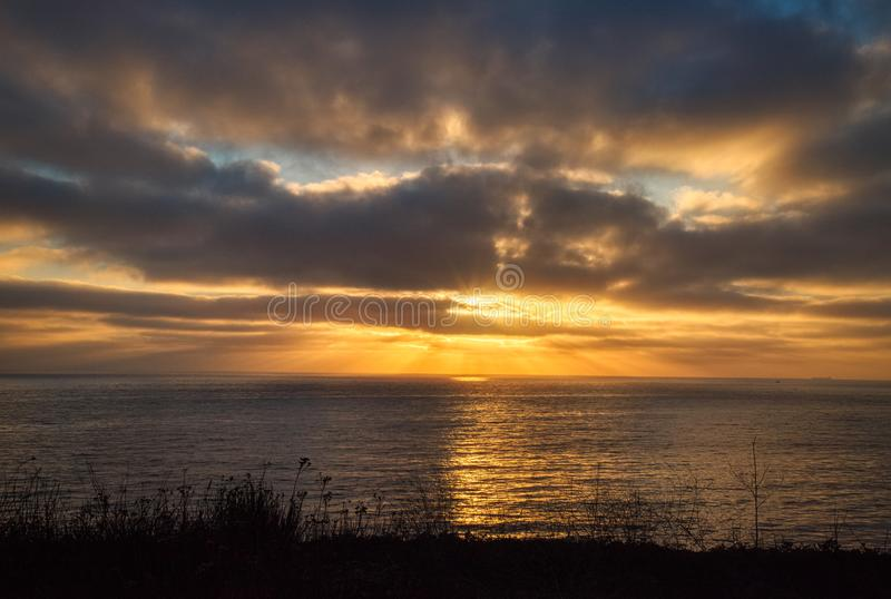 Dramatic Coastal Sunset from Rancho Palos Verdes. Dramatic coastal sunset with beams of sunlight shining through the clouds from Terranea Trail, Rancho Palos stock images