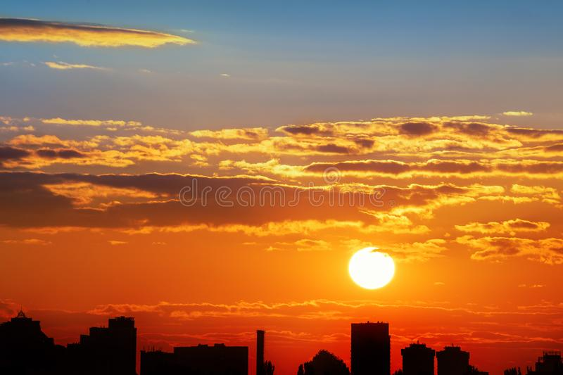 Dramatic colorful fiery red sunset or sunrise sky landscape with line row of city buildings silhouettes . Natural beautiful royalty free stock image
