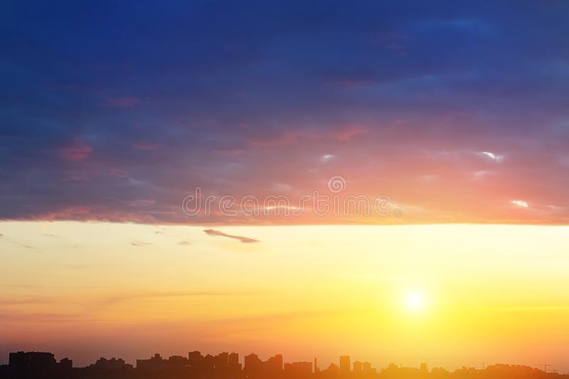 Dramatic colorful sunset or sunrise sky landscape with line row of city buildings silhouettes . Natural beautiful cityscape dawn. Background wallpaper royalty free stock photos
