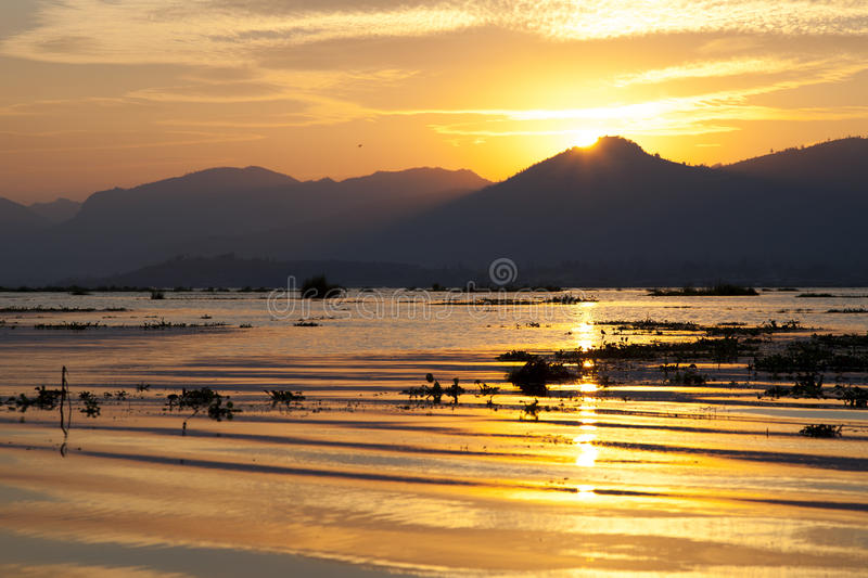 Sunset on Inle Lake. Dramatic colors of sunset drift across Inle Lake in Myanmar stock image