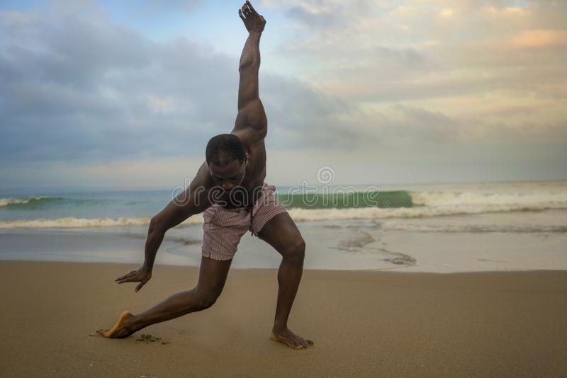 Dramatic contemporary dance choreographer doing ballet beach workout, young attractive and athletic afro black American man. Dramatic contemporary dance stock photo