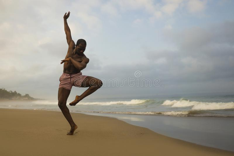 Dramatic contemporary dance choreographer doing ballet beach workout, young attractive and athletic afro black American man royalty free stock photo