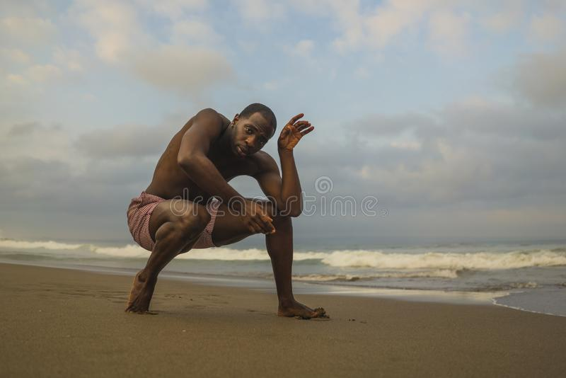 Dramatic contemporary dance choreographer doing ballet beach workout, young attractive and athletic afro black American man stock images