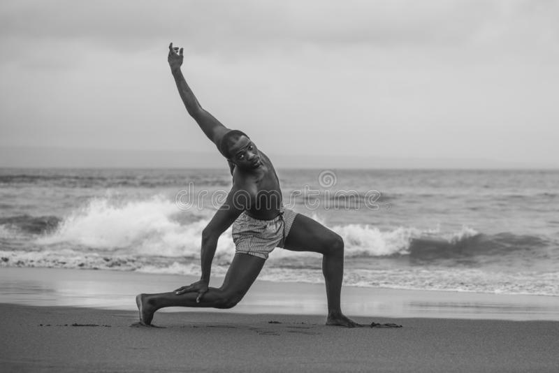 Dramatic contemporary dance choreographer doing ballet beach workout, young attractive and athletic afro black American man royalty free stock image