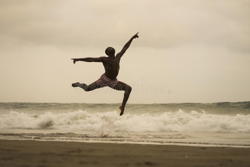 Contemporary dance choreographer doing ballet beach workout . young attractive and athletic black African American man dancing on. Dramatic contemporary dance royalty free stock images