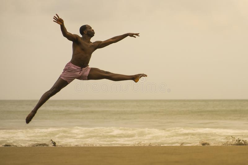 Contemporary dance choreographer doing ballet beach workout . young attractive and athletic black African American man dancing on. Dramatic contemporary dance royalty free stock image