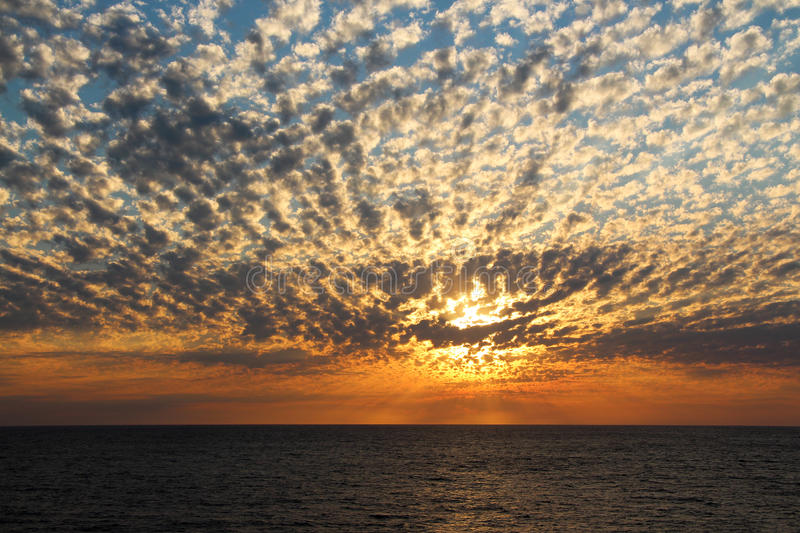 Dramatic cumulus clouds. At sunset over the ocean stock photo
