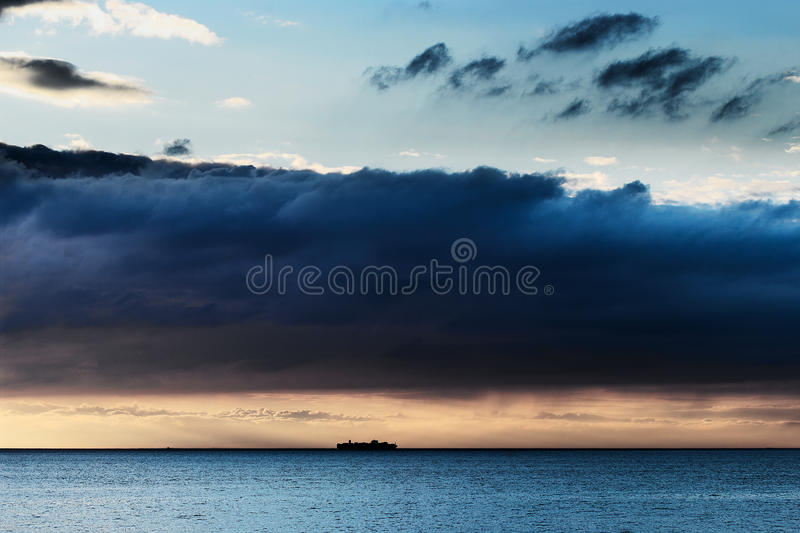 Dramatic dark nimbostratus cloud formation over Baltic sea and small ship silhouette. royalty free stock photography