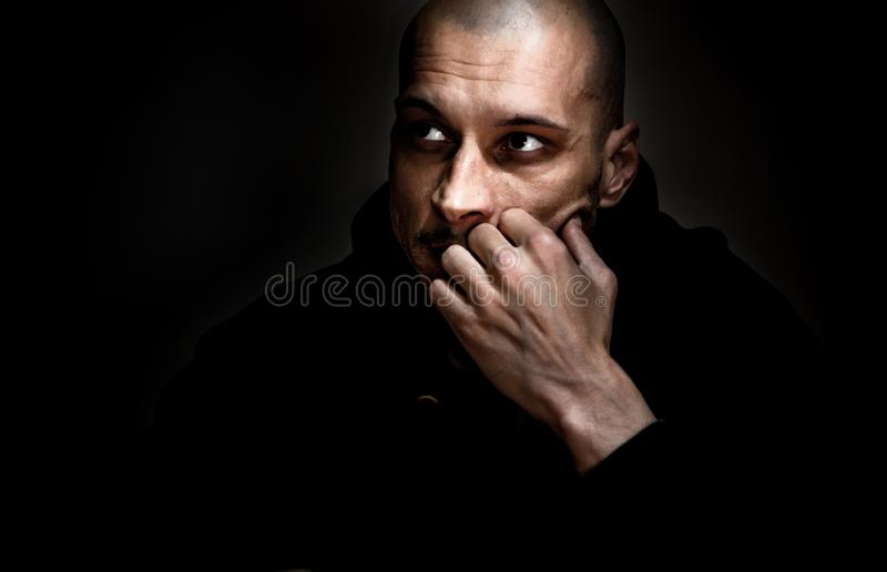 Dramatic dark portrait with strong contrast and film grain of young man sitting in the room with sadness and depression in his eye stock photos