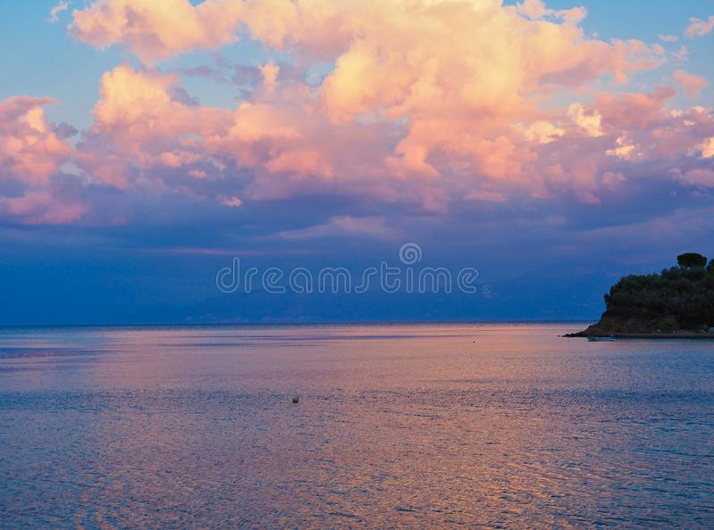 Dramatic Sunset Light on Clouds and Sea water, Greece. A dramatic Gulf of Corinth sunset, with orange to pink sunset-dusk light on clouds and reflected in the royalty free stock images