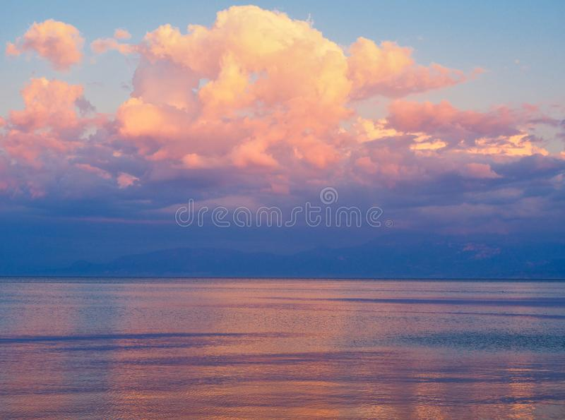 Dramatic Sunset Light on Clouds and Sea water, Greece. A dramatic Gulf of Corinth sunset, with orange to pink sunset-dusk light on clouds and reflected in the stock photos