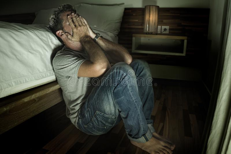 Dramatic home portrait of young desperate and depressed lonely man sitting on bedroom floor crying sick suffering anxiety crisis royalty free stock photography
