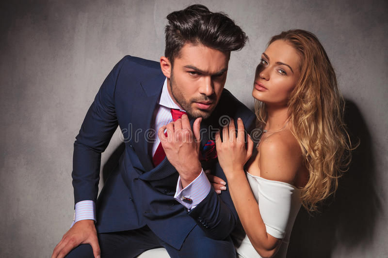 Dramatic hot elegant couple sitting embraced. And looking at the camera stock photos